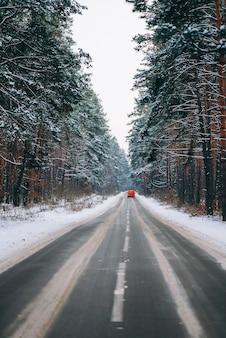 Rijdende auto op een bosweg in de sneeuw