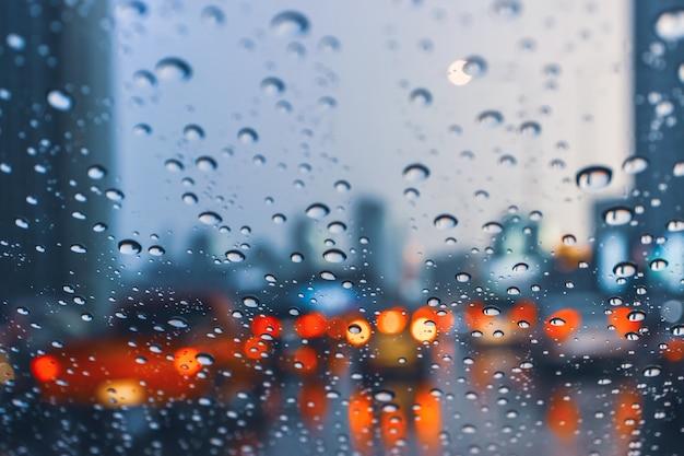 Rijdende auto op metropoolweg in verkeersopstopping met regendruppel over het windschild