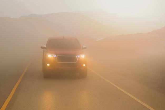 Rijdende auto's in de mistberg met koplampstralen in dichte mist.