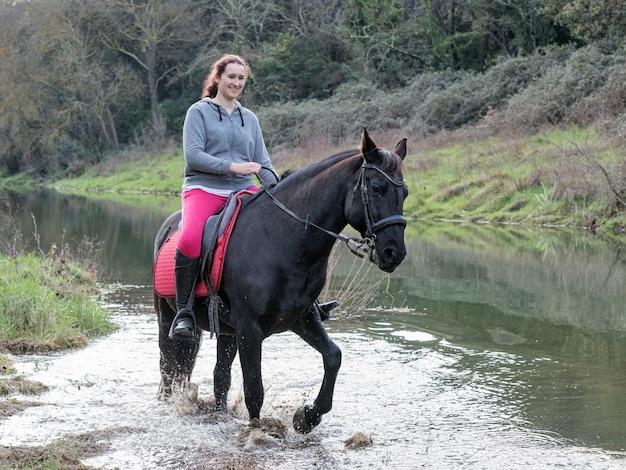 Rijdende meid traint haar zwarte paard