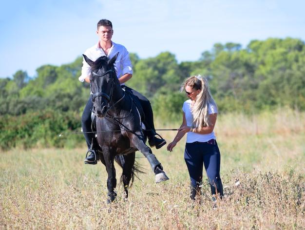 Rijdende tiener, leraar en paard