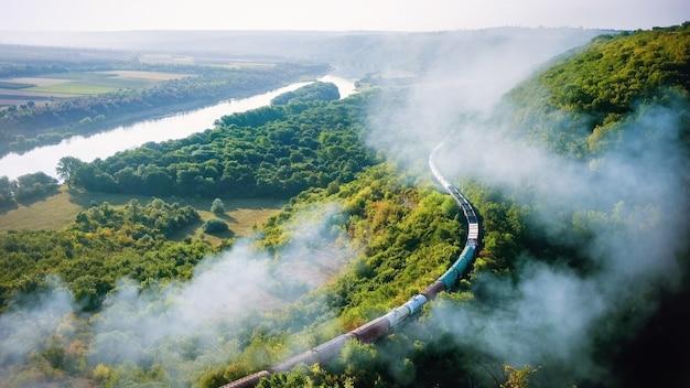 Rijdende trein op spoor met hoge rookkolom, stromende rivier, heuvels en spoorlijn op de voorgrond