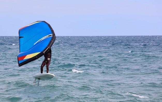 Rijder op een windfoilboard surfen op de golven