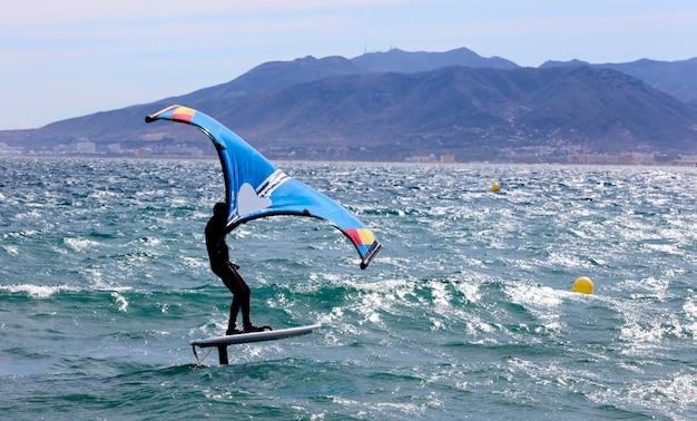 Rijder op een windfoilboard surft over de golven, bergen op de achtergrond