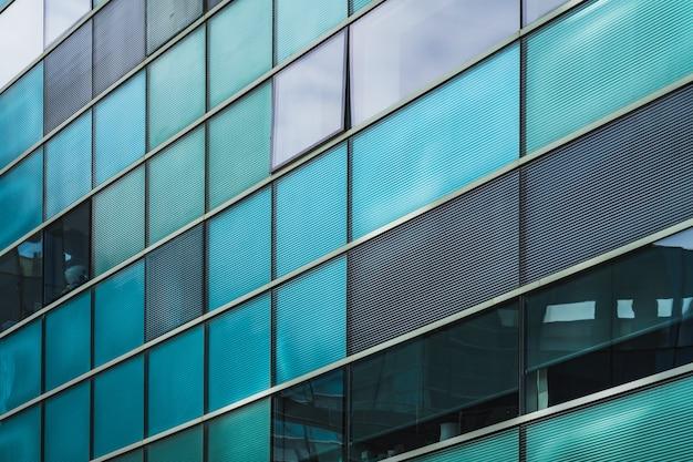 Rijen blauwachtige en groenachtige ramen op de glazen gevel van een stedelijk gebouw
