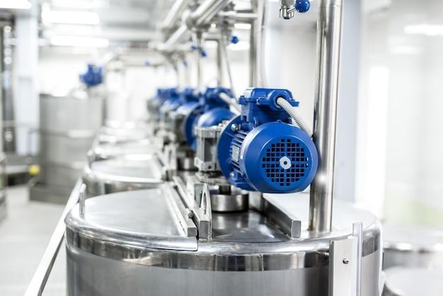 Rijen blauwe elektromotoren op tanks voor het mengen van vloeistoffen. roestvrij staal, voedingsindustrie.