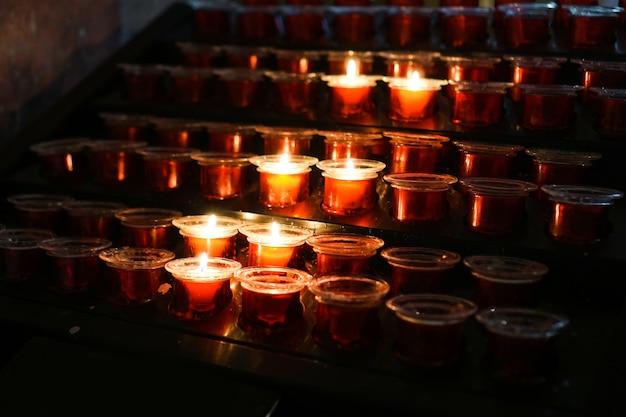 Rijen brandende kaarsen in een schemerige kerk