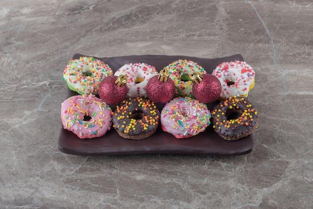 Rijen donuts en kerstballen gerangschikt op een schaal op marmeren oppervlak