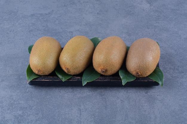Rijen kiwi's met bladeren op het bord op het donkere oppervlak