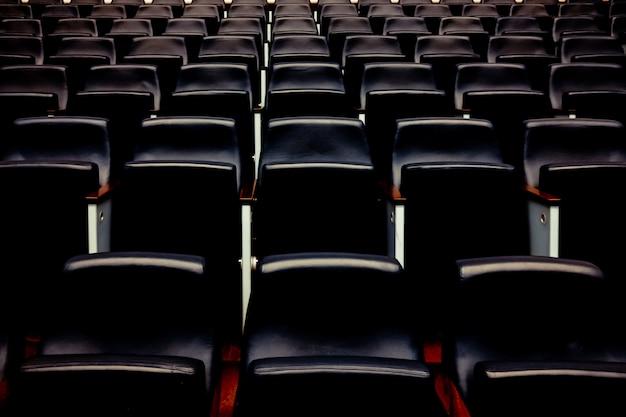 Rijen lege stoelen en stoelen in een auditorium.
