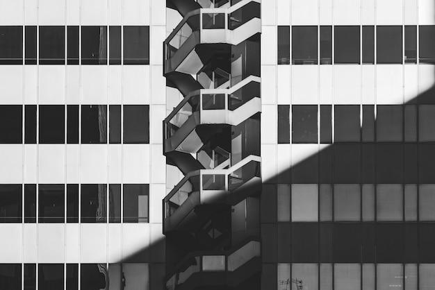 Rijen met glazen ramen en buitentrap van de gevel van een kantoorgebouw in zwart-wit