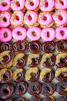 Rijen met kleurrijke donuts verwerken in herfstkleurstijl en genomen vanuit bovenaanzicht.
