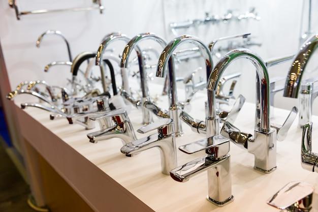 Rijen met nieuwe kranen in sanitair winkel, close-up