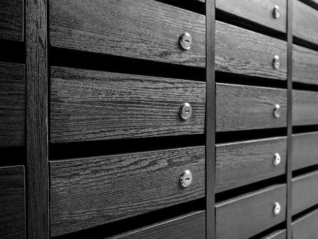 Rijen met ongenummerde houten brievenbussen en kluisjes