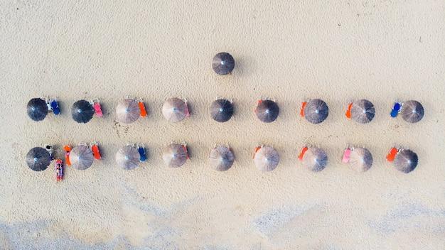 Rijen parasols van riet met daaronder ligbedden op het strand Premium Foto