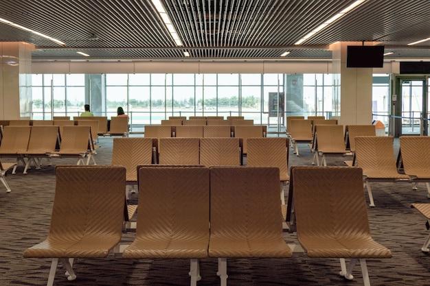Rijen passagiersstoel voor de vertrekhal op de luchthaven
