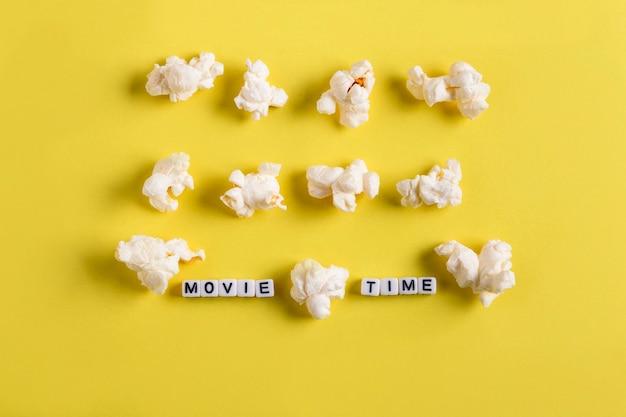 Rijen popcorn en in het midden het woord filmtijd op een gele achtergrond filmplan concept