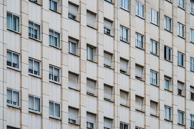 Rijen ramen met rolluiken op de gevel van een stedelijk gebouw