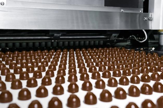 Rijen toppings voor machinaal vervaardigde chocolaatjes, op een transportband van een chocoladefabriek