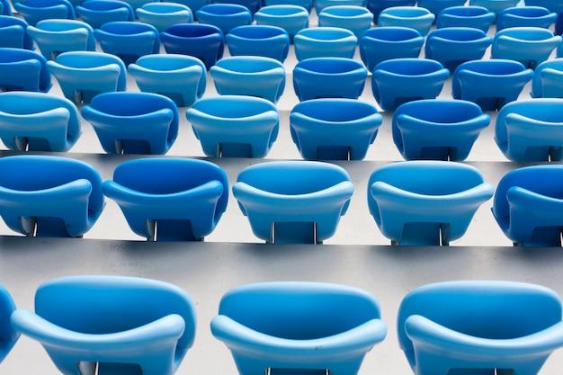 Rijen van blauwe zetels bij voetbalstadion.