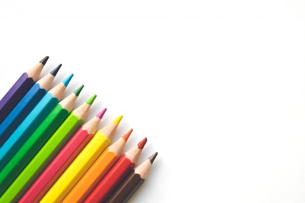Rijen van kleurenpotloden op witboekachtergrond, exemplaarruimte. kantoorbenodigdheden, terug naar school.
