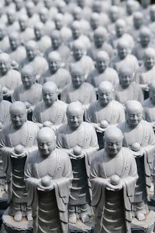 Rijen van soortgelijke japanse jizo-sculpturen in de hase-dera-tempel, kamakura, japan