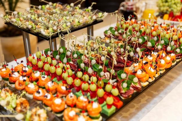 Rijen verrukkelijke hapjes op de feesttafel. catering voor zakelijke bijeenkomsten, evenementen en feesten.