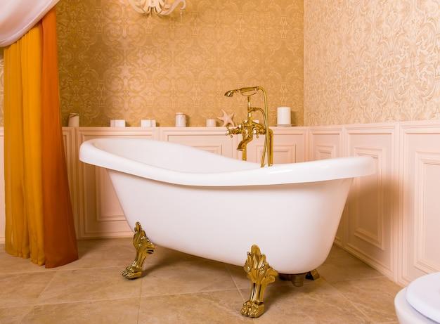 Rijk bad met roltoppen in de vorm van dierenpoten en gouden kraan in de badkamer. luxe sanitair