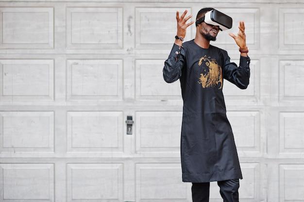 Rijke afrikaanse man in stijlvolle traditionele kleding in vr-bril. toekomst van afrika concept.