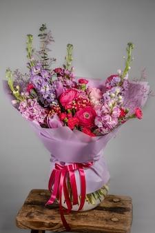 Rijke bos roze en rode bloemen en lila. eustoma rozen bloemen bloeien, groen blad in glazen vaas. fris lenteboeket. zomer achtergrond