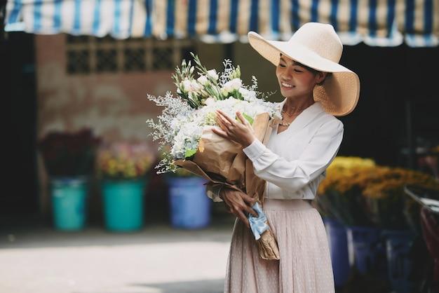 Rijke chique aziatische vrouw die groot boeket bewondert dat bij bloemenwinkel wordt gekocht