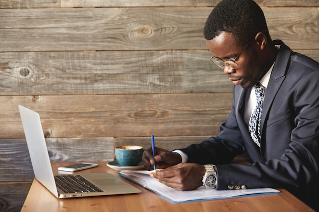 Rijke en ernstige donkere zakenman met laptop die rapport controleert