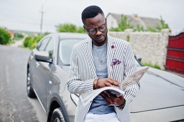 Rijke en stijlvolle afro-amerikaanse man in blazer en witte broek, bril gelezen tijdschrift tegen zijn suv auto.