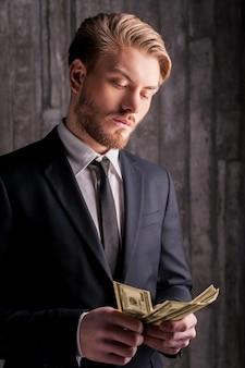 Rijke knap. knappe jonge man in formalwear die geld telt