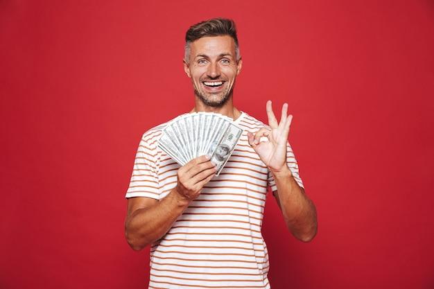 Rijke man in gestreept t-shirt glimlachend en met fan van geldbankbiljetten geïsoleerd op rood