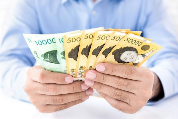 Rijke professionele zakenman die contant geld koreaans geld houdt