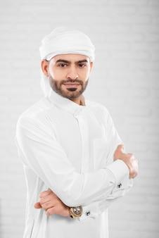 Rijke rijke knappe succesvolle moslim man in traditionele islamitische kleding poseren