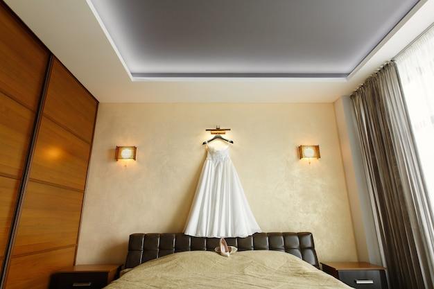Rijke trouwjurk op een hanger aan de muur. ochtend van de bruid in de hotelkamer. mooie witte trouwjurk voor bruid binnenshuis in de slaapkamer. trouwdag.