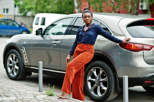 Rijke zakelijke afrikaanse vrouw in oranje broek en blauw shirt gesteld tegen zilveren suv auto