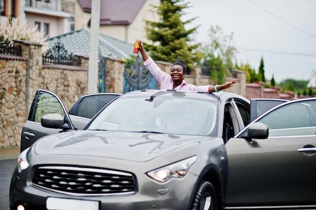 Rijke zakelijke afrikaanse vrouw in zilveren suv auto op zonnedak plezier met bier in de buurt