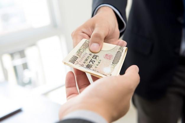 Rijke zakenman die geld, japans yen contant geld geeft, aan zijn partner