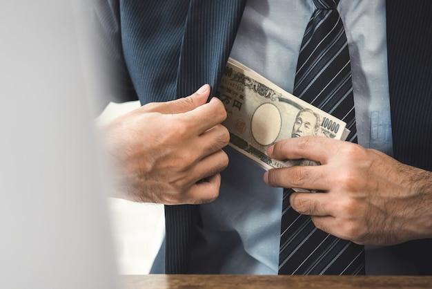 Rijke zakenman die het japanse geld van het yenbankbiljet houdt in zijn kostuumzak
