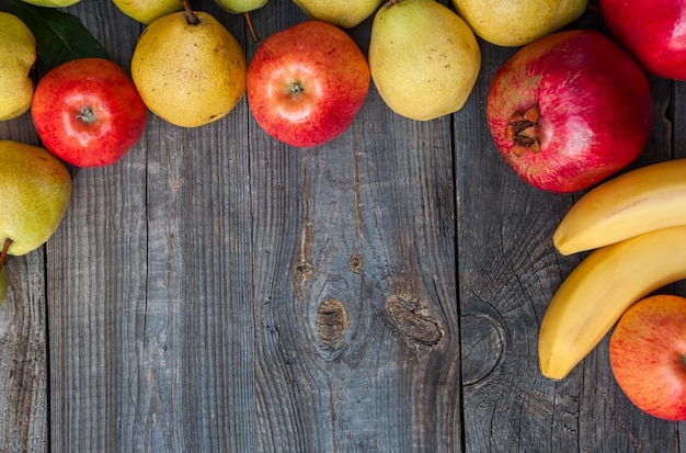 Rijp fruit gevoerd kader op een grijze houten oppervlakte, lege ruimte in het midden