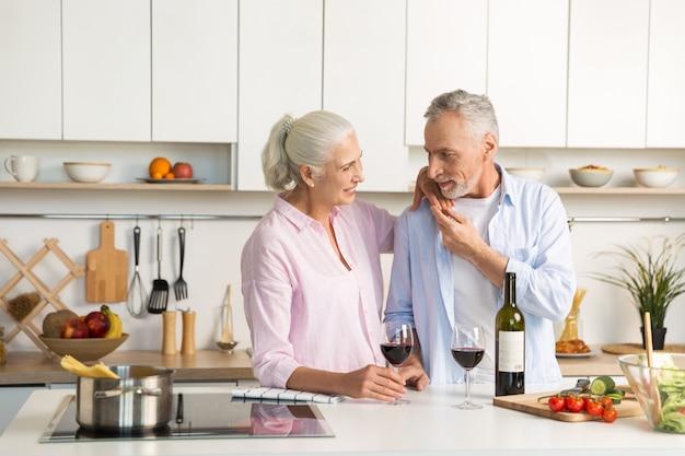 Rijp gelukkig houdend van paar die zich bij de keuken het drinken wijn bevinden