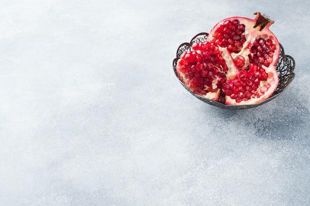 Rijp granaatappelfruit in een uitstekende plaat op een grijze geweven achtergrond. kopieer ruimte.