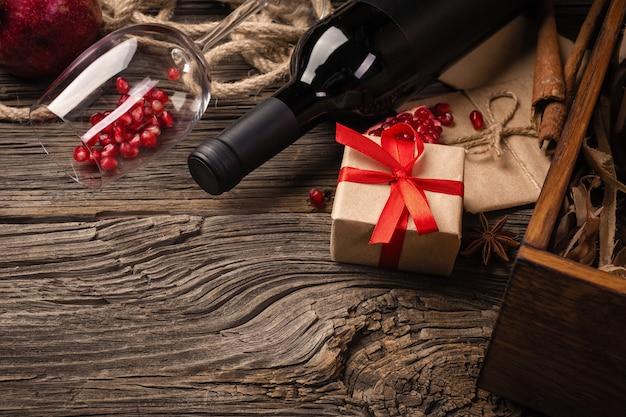 Rijp granaatappelfruit met een glas wijn, een fles en een geschenk