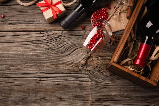 Rijp granaatappelfruit met een glas wijn, een fles en een gift op een houten achtergrond