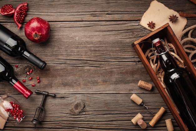 Rijp granaatappelfruit met een glas wijn, een fles in een doos op een houten achtergrond