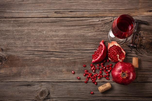 Rijp granaatappelfruit met een glas wijn en een kurketrekker op een houten achtergrond