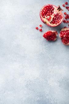 Rijp granaatappelfruit op een grijze geweven achtergrond.